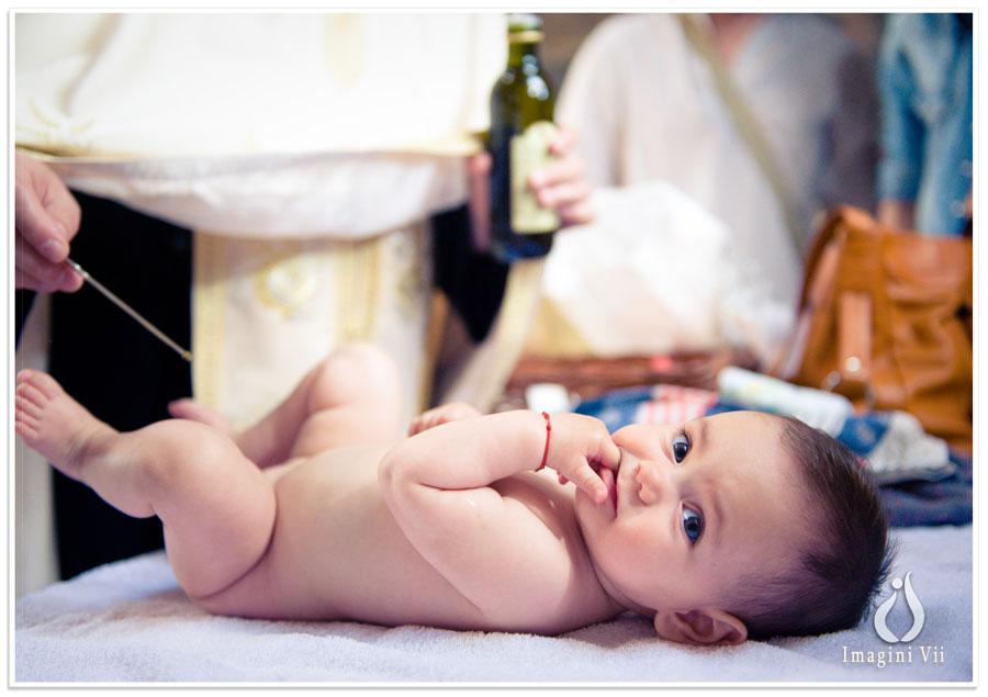 Fetiță așezată pe fașă la slujba de botez