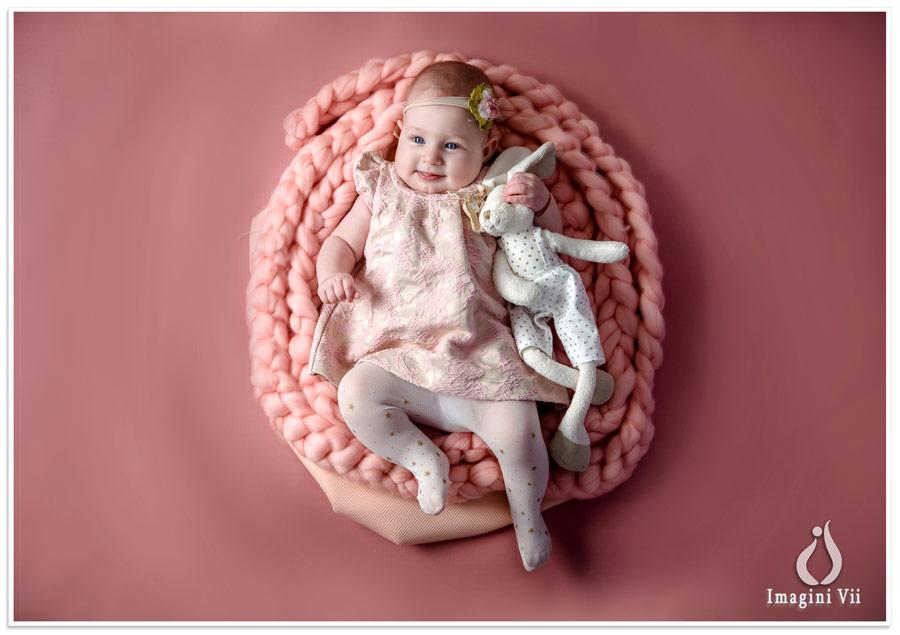 Fetiță cu jucărie de pluș pe un pătuț împletit